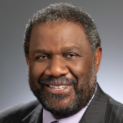 photo of Ralph Smith, smiling, wearing gray pinstriped suit with pink dress shirt