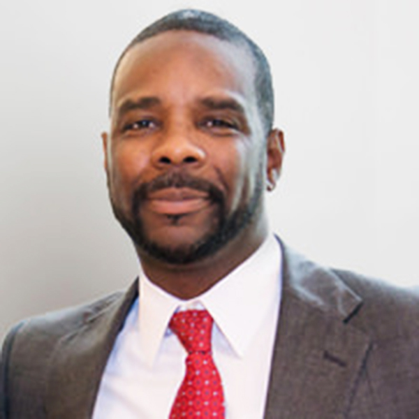 photo of Kareem Weaver, smiling, wearing gray suit with red polka-dot tie